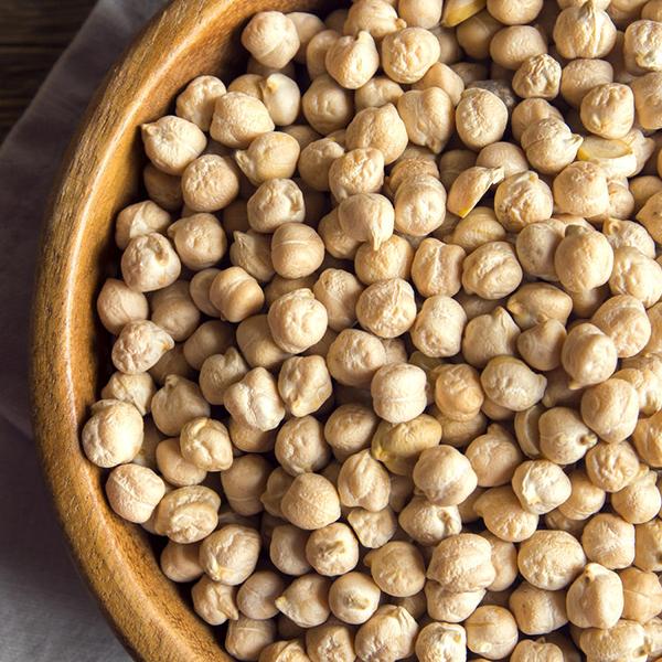 Raw organic chickpeas in rustic wooden bowl, healthy vegan food